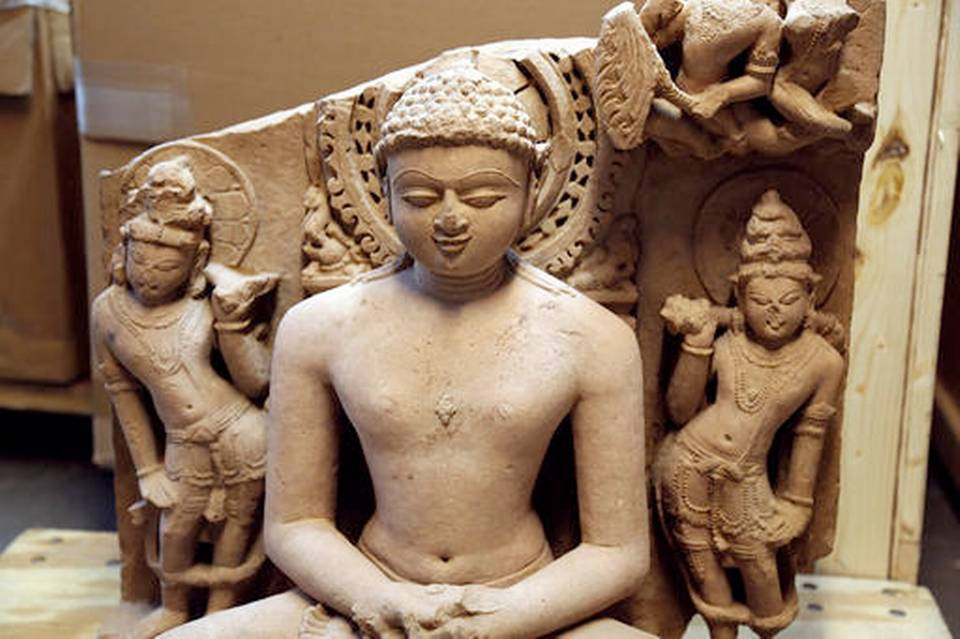 A sandstone statue of Rishabhanata, from Rajasthan or Madhya Pradesh, India, in the 10th century A.D., flanked by a pair of attendants. It is valued at approximately $150,000